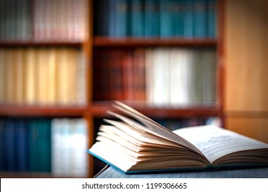 Open book on a table,on the background of bookshelves