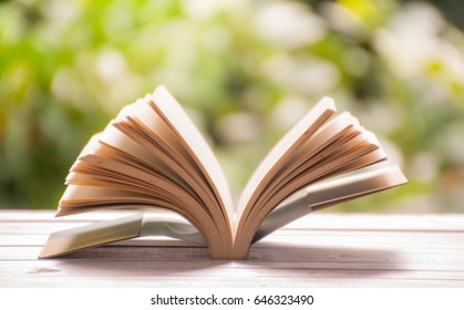Open book on white table against nature background