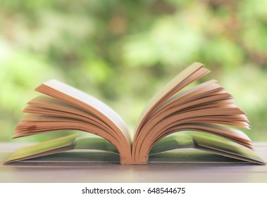Open book on white table with nature background