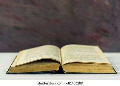 Open book on an white wooden table. Beautiful background.