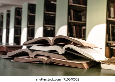 Open book on wood desk in the library room with blurred focus for background