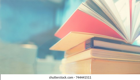 Open book on wood desk in the library room with blurred focus for background, education back to school concept, vintage color tone process