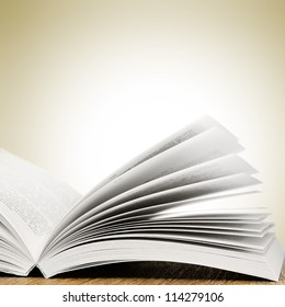 Open book on wood table over white background. With place for text