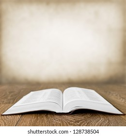 Open book on wood table over grunge background
