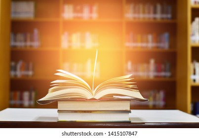 Open Book on wood table and blurred bookshelf in the library, education background, back to school concept.