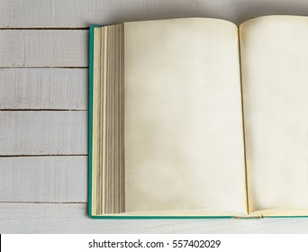 Open book on wooden background. Back to school. Copy space. Top view. Toned retro image.