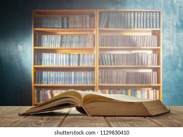 An open book on a wooden table and a bookcase