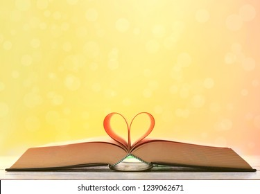 Open book on wooden table on orange blurred background. Heart book page.