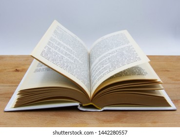 Open book on wooden table, white background
