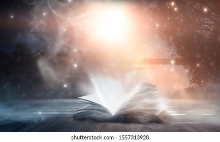 An open book on a wooden table under the night sky against a dark forest. Magical radiance. Night scene.