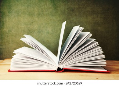 open book on wooden table on textured vintage background