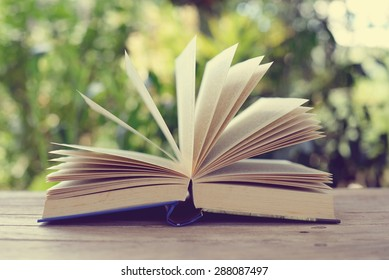 open book on wooden table with nature background.