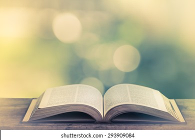 open book on a wooden table in nature, green blurry background