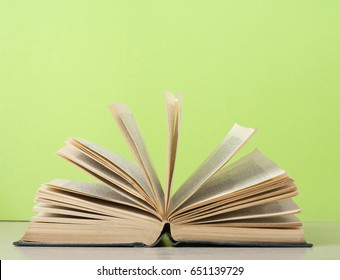 Open book on wooden table on the background of green wall. Copy space for text.Back to school. Education concept.