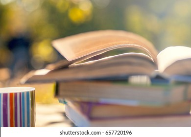 Open book on wooden table on natural background. Toned image. Soft focus