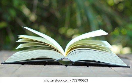 the open book on the wooden table with the blur nature background, in concept of education, textbook, academic, learning, student, university, research