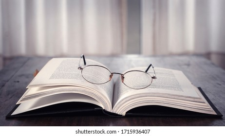 Open book over wooden table with glasses on it. Library. Literature. Read. Study.