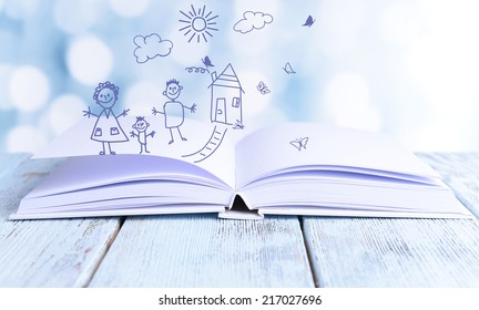 Open book with paintings on bright background
