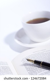Open book with a pen and a cup of coffee, close up