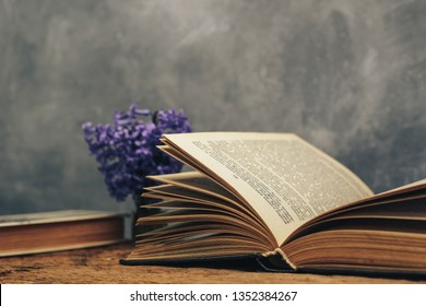 Open book and purple flower on a old  oak wooden table. Gray wall background.