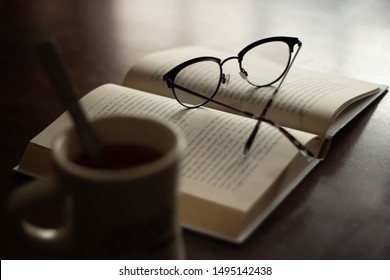 Open book with reading glasses next to a cup of hot coffee or tea, focus on glasses, reading relax refresh break time out solitude concept, brain food nourish yourself start the morning right concept
