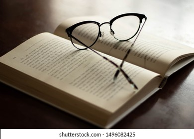 Open book with reading glasses next to window with light coming in, focus on glasses frames with surrounding area out of focus, enlightenment knowledge wisdom education clarification concept