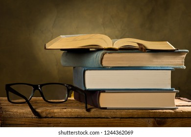 Open book with reading glasses on the dark background
