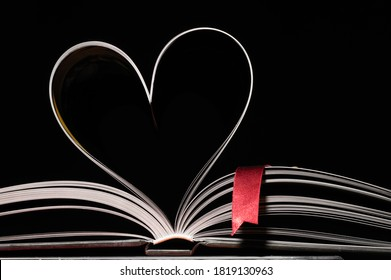 Open book with red book cover on black background. Pages in the shape of a heart. Close-up.