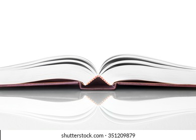 Open book with reflection. Low angle edge view of book spine and pages on reflective surface. Isolated on white background with copy space.