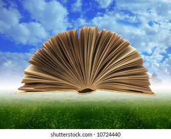 open book at sky background under green grass