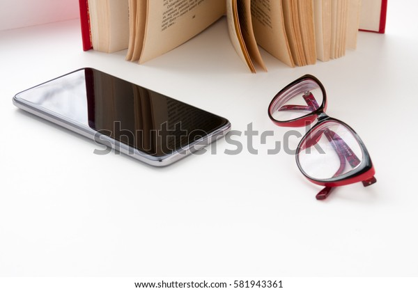 Open book, smartphone and red glasses on the table