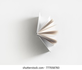 Open book with soft shadow on white paper background.