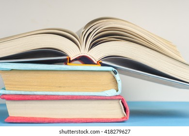 Open book, stack of colorful hardback books on light table. Back to school. Copy space for text. Toned image.