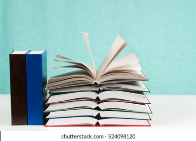 Open book, stack of hardback books on table. Back to school. Copy space.