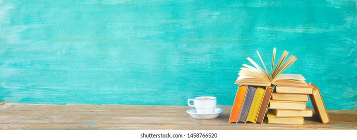 Open Book and stack of multicolored hardback books with a cup of coffee, reading education, literature concept. Panoramic, mock up, banner template, free copy space