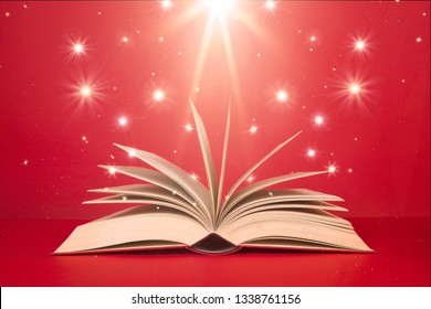 Open book with stars and bright light on a red background as if it were magic