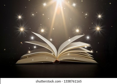 Open book with stars and bright light on a black background as if it were magic