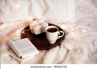 Open books, candles and cup of tea on wooden tray in bed. Good morning. Leisure time.