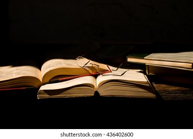 Open books with reading glasses on black background
