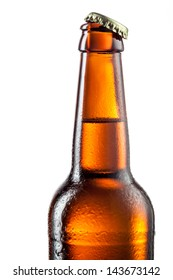 Open bottle of beer with drops isolated on white