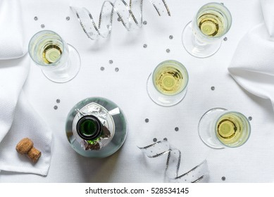 Open bottle of bubbly with four flute stemware