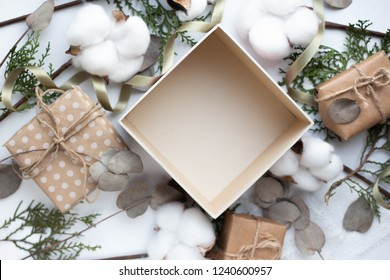 open box with eucalyptus leaves and cotton flowers and gift boxes on white background. Flat lay, top view. copy place