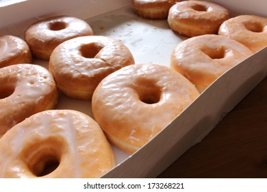 Open box of glazed doughnuts with a few missing