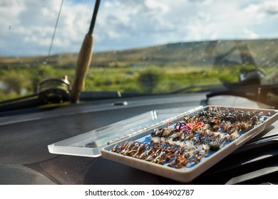 Open box of hand tied fly fishing flies inside a car with a rod and reel visible through the window and a view of green countryside