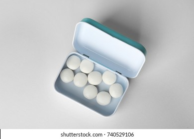 Open box with hard mint candies on light background