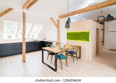 Open bright kitchen with black kitchen cabinets and table. Modern bright flat apartment in the attic. Kitchen with black kitchen cabinets