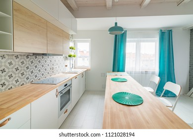 Open bright kitchen with white furniture. Island kitchen. Turquoise lamps and curtains. Modern, bright attic apartment.
