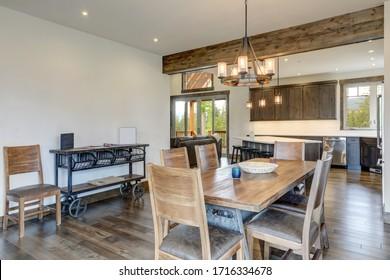 Un salon ouvert et lumineux avec une longue table en bois rustique et un mobilier moderne en métal et une charrette en guise de table latérale.