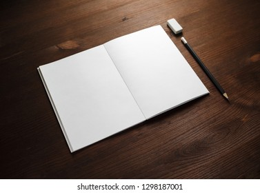 Open brochure with blank pages, pencil and eraser on wooden background. Responsive design template.