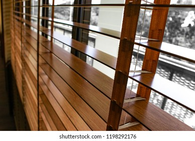 Open brown wooden shutters blinds (Jalousie or Windows blinds) used to control and protect the light in the room
